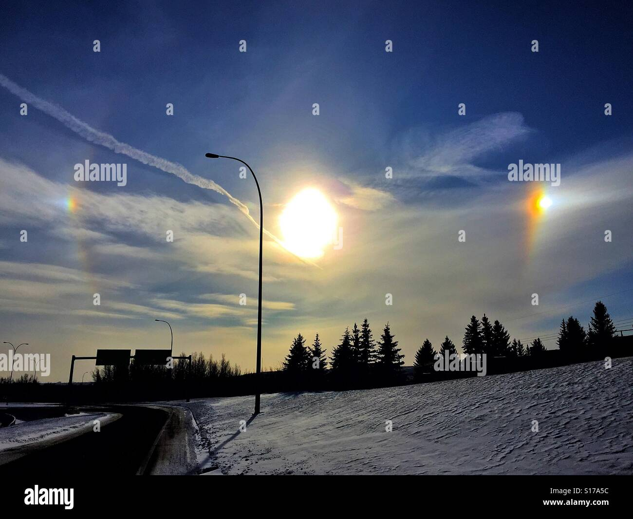 Bright sun, sun dogs, and jet stream - Stock Image