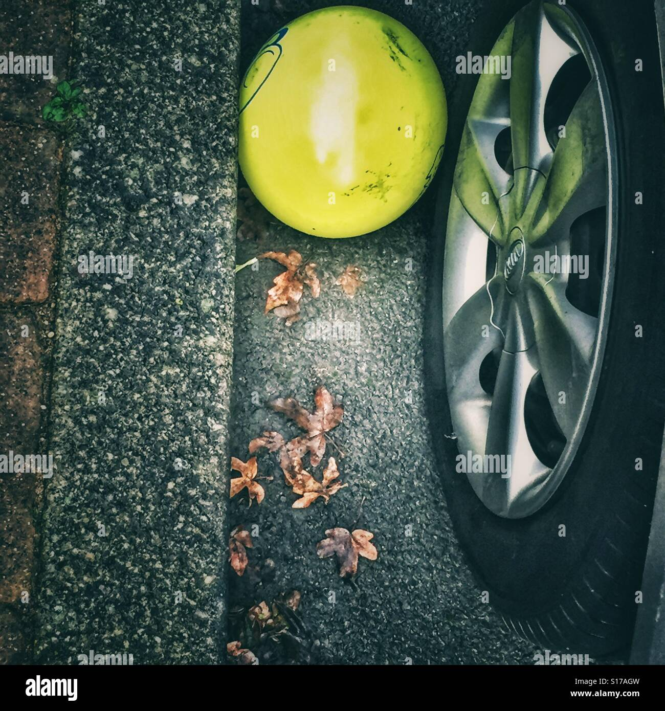 Abandoned Yellow balloon wedged between a tire of a car and a pavement - Stock Image
