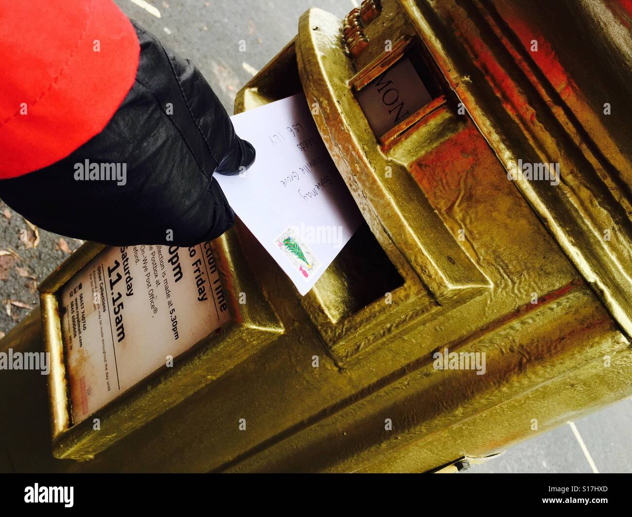 Posting a letter in a gold painted Royal Mail postbox UK - Stock Image