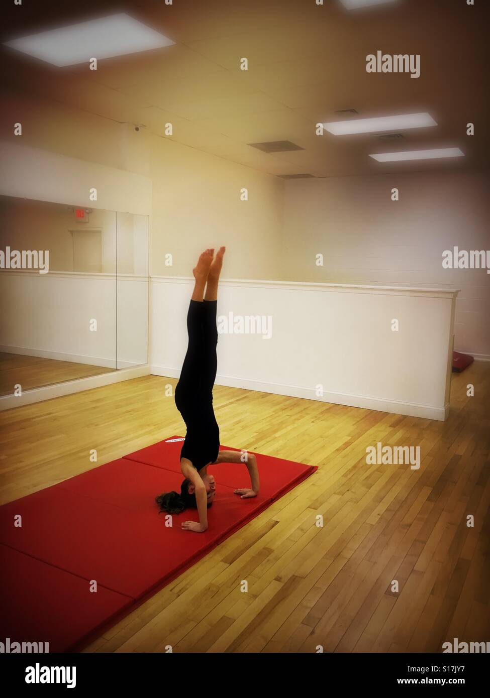 Girl doing headstand in acrobatics class - Stock Image