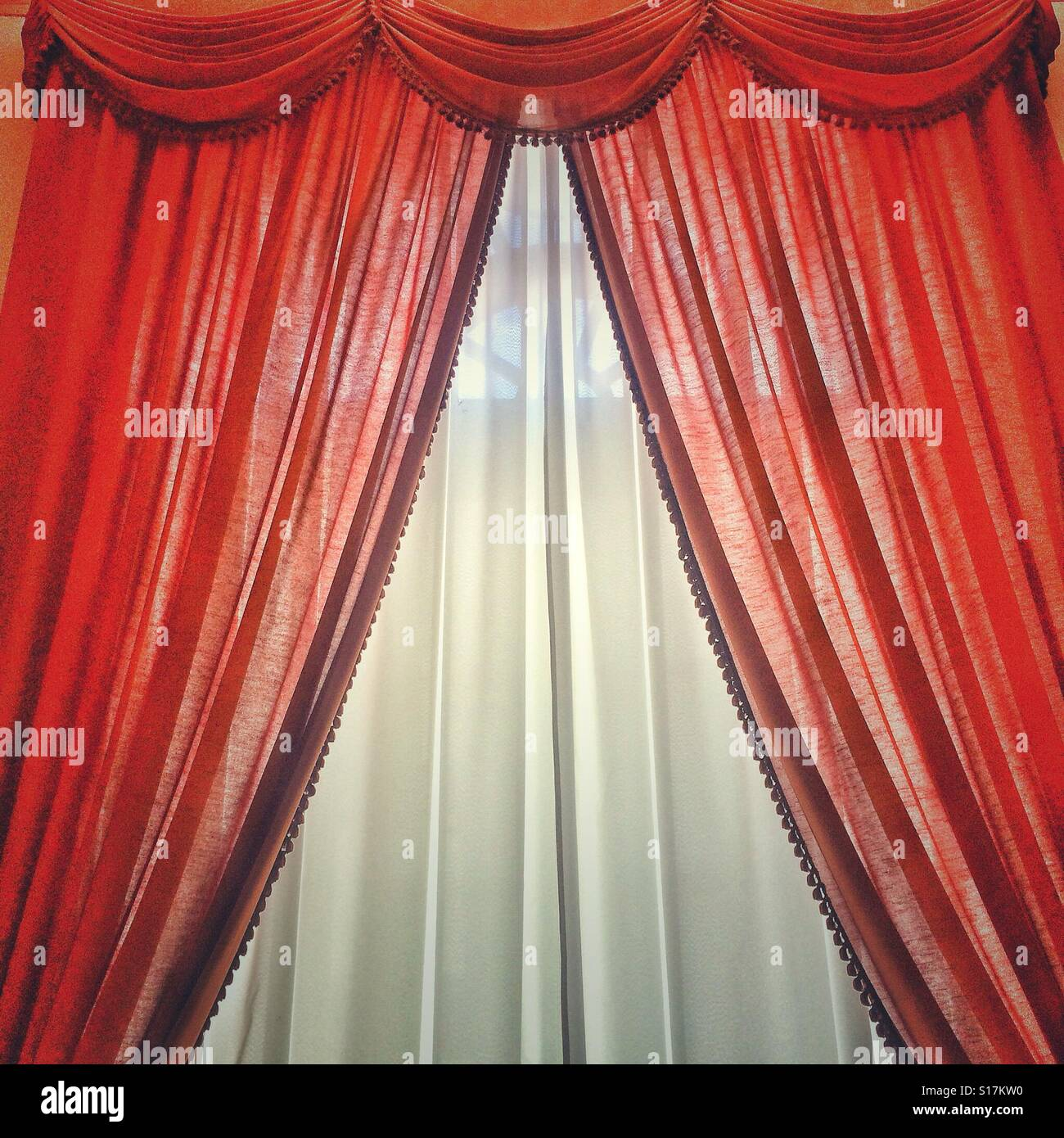 Bright red and white curtains - Stock Image