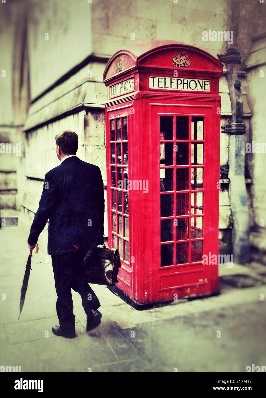 A city gent walking by an iconic red telephone box in central London. - Stock Image