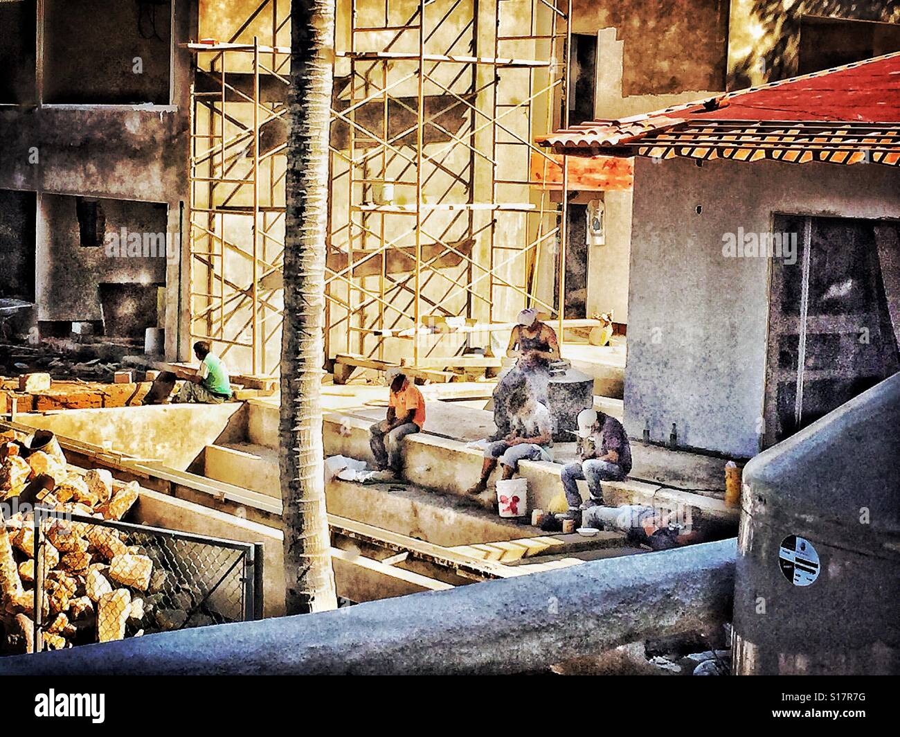Construction site with workers on a break using their cell phones. - Stock Image