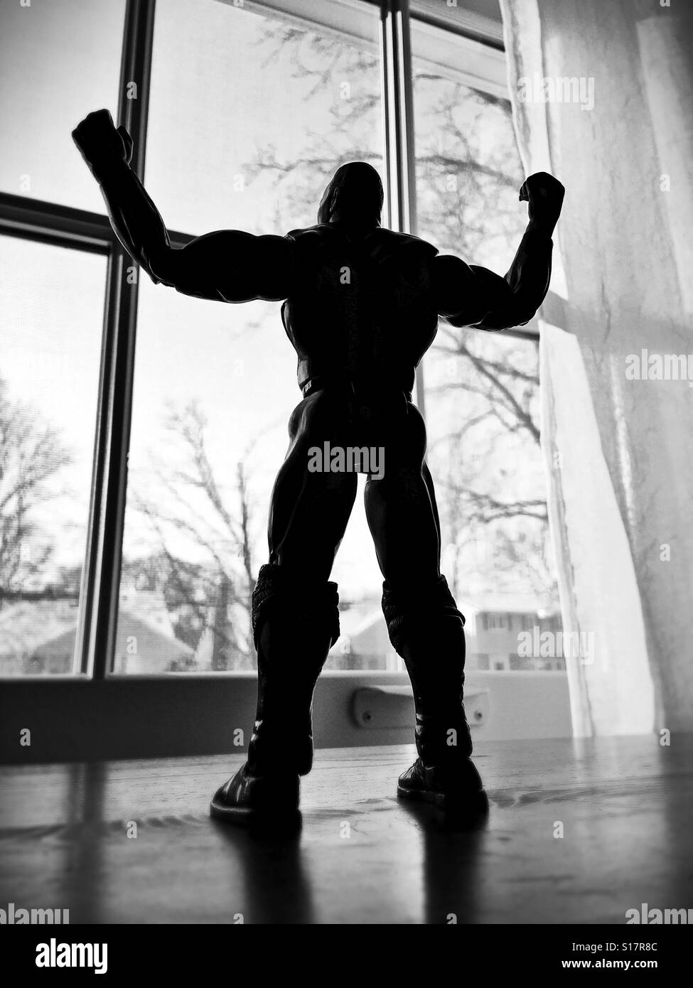 A muscled male action figure posed as if looking out a window with arms raised in victory. - Stock Image