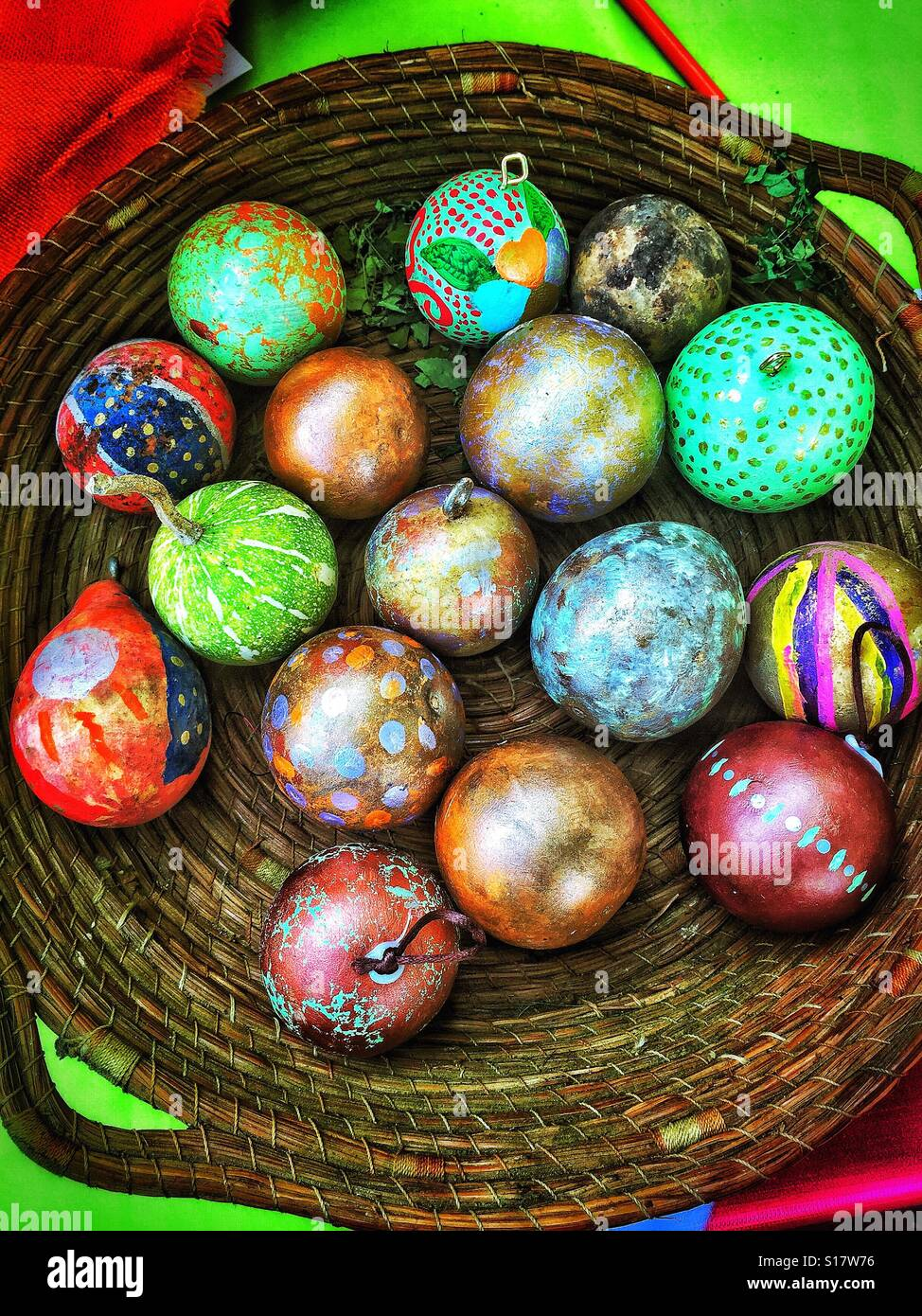 A natural material bowl is filled with painted gourds for unique one of a kind decorations. - Stock Image