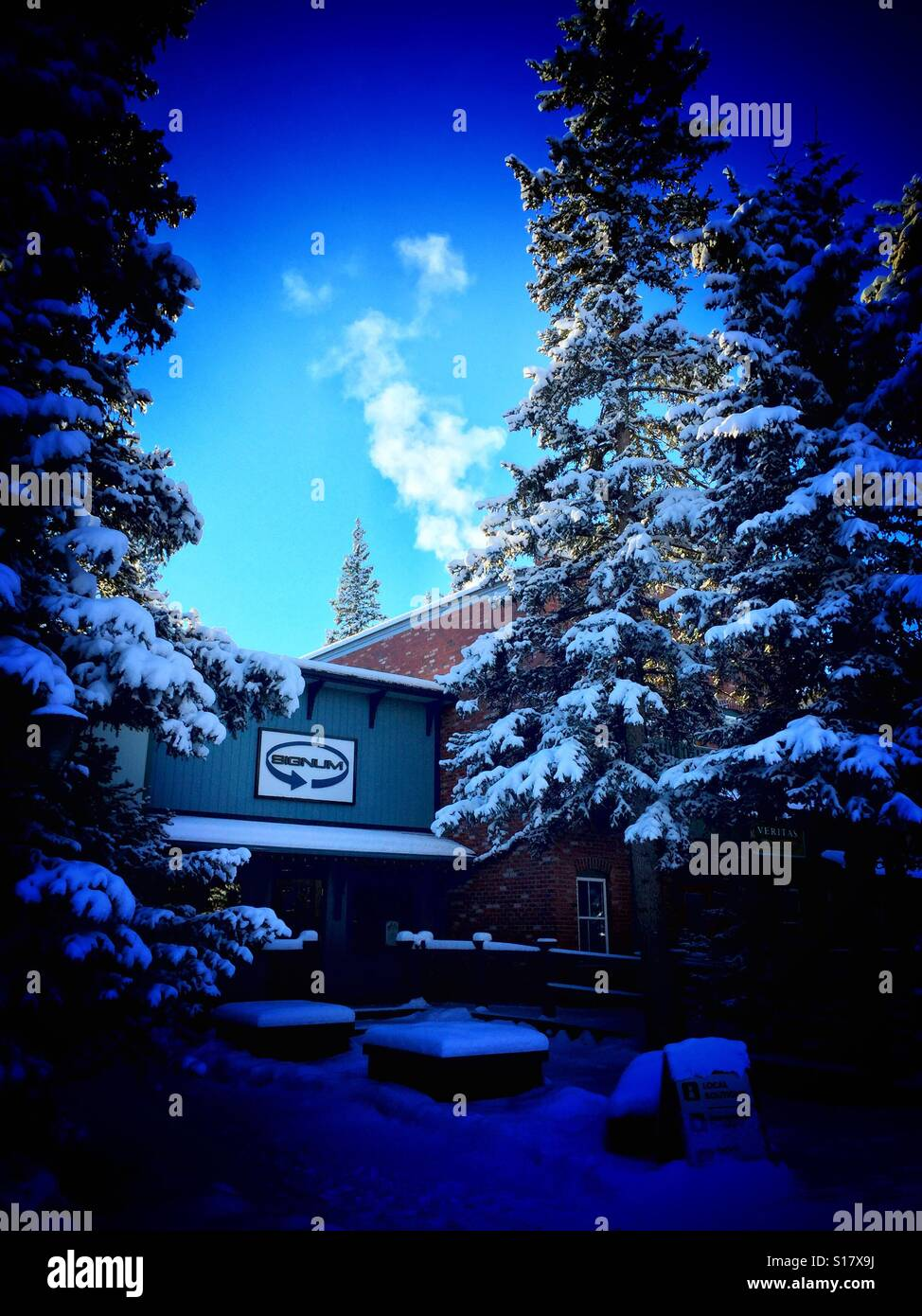 Bragg creek strip mall surrounded by snow covered evergreens with exhaust from one of the businesses - Stock Image
