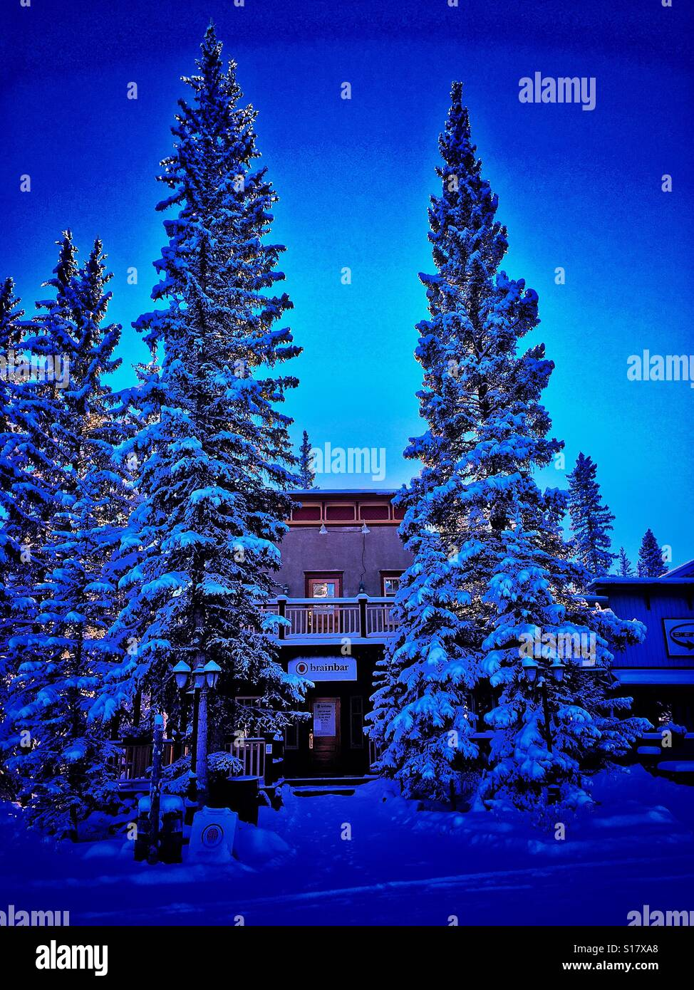 Village of Bragg Creek strip mall surrounded by snow covered evergreens - Stock Image