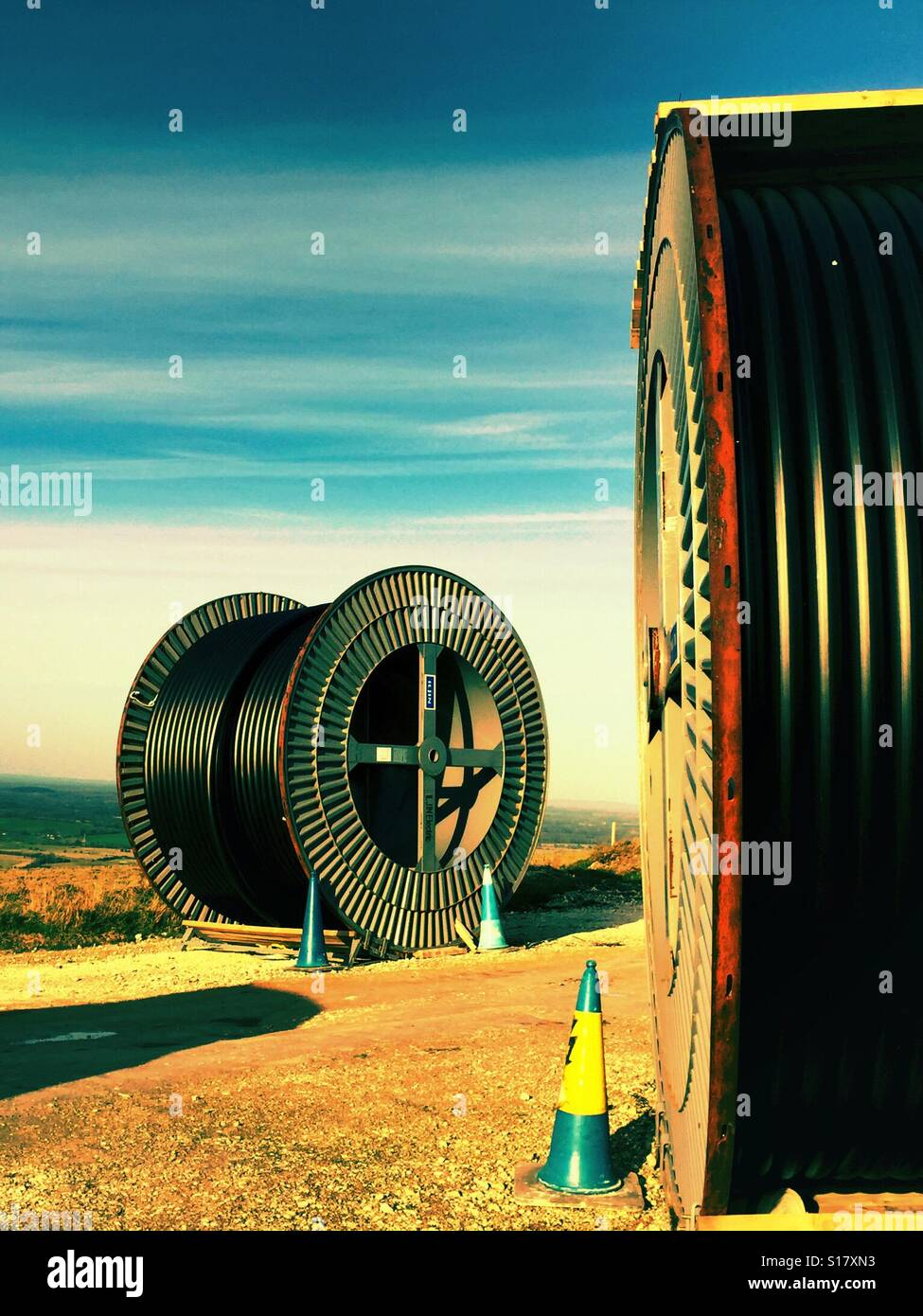 Reels of electric cabling in the countryside. - Stock Image