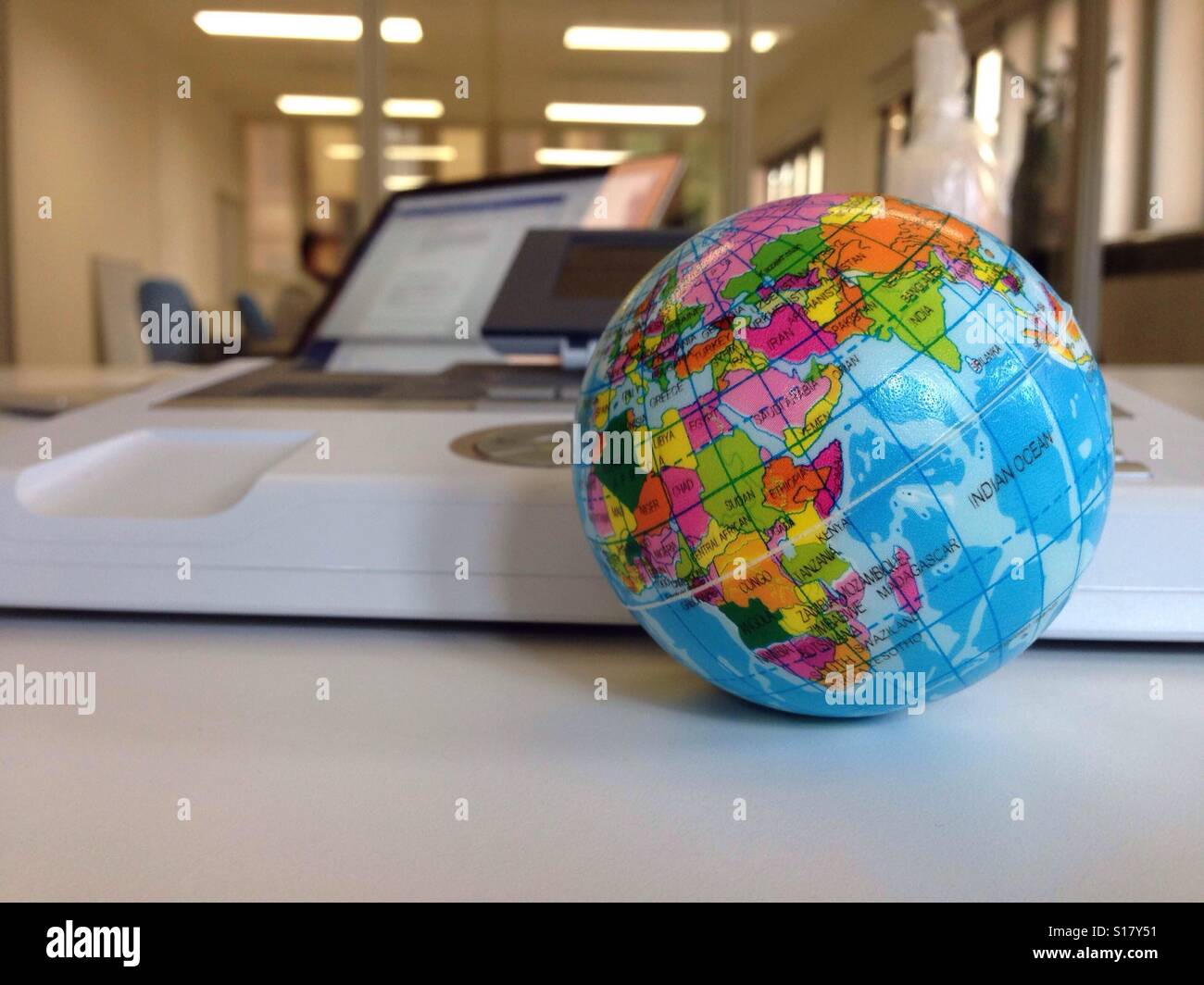 World Globe On An Office Desk, With Telephone And Laptop In Background.    Stock