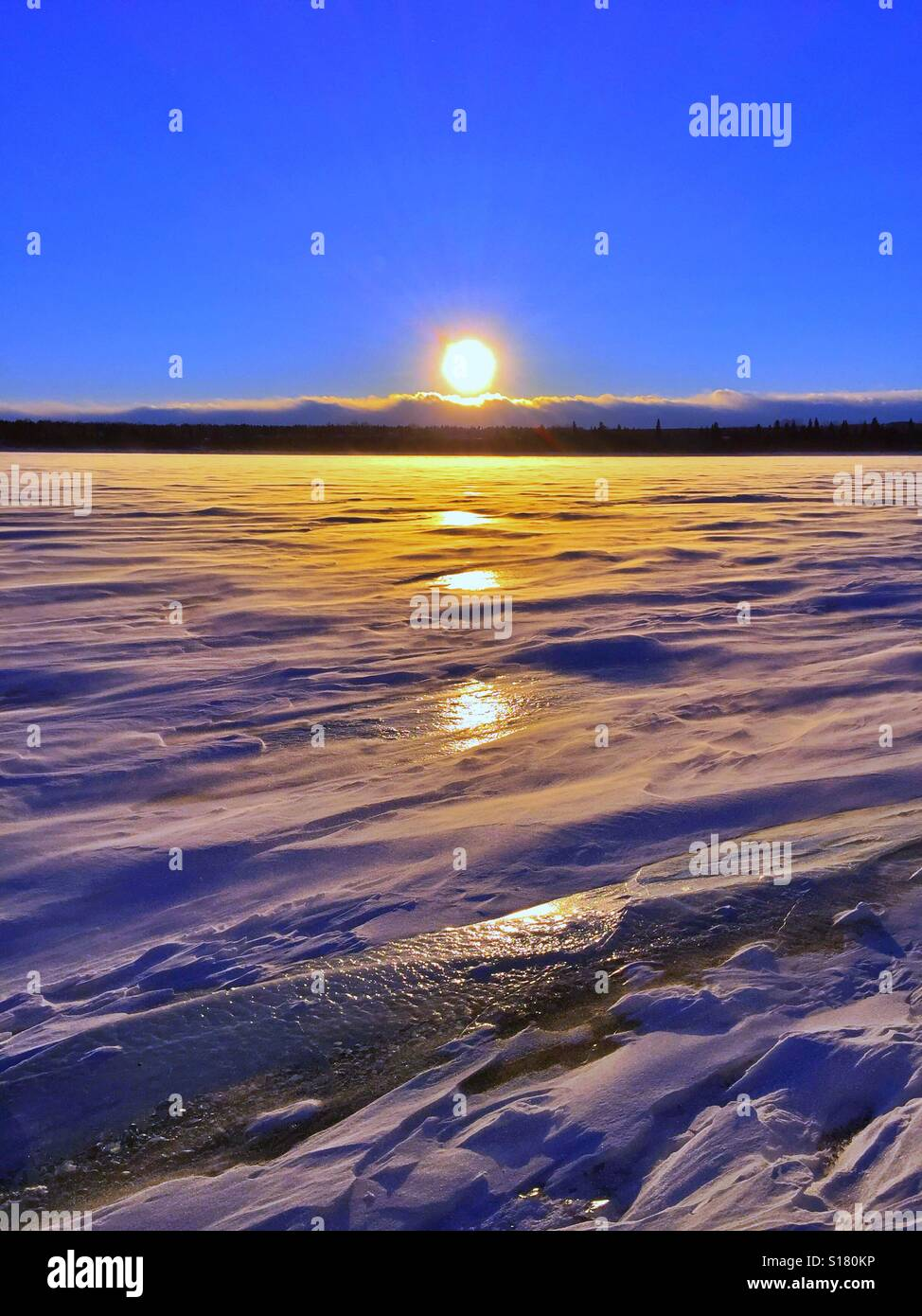 Setting sun and reflections on a lake - Stock Image