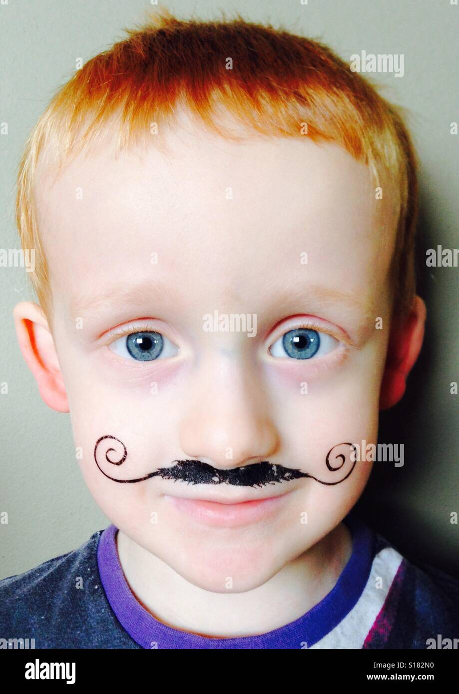 Red haired, blue eyed boy with a curly drawn on moustache - Stock Image