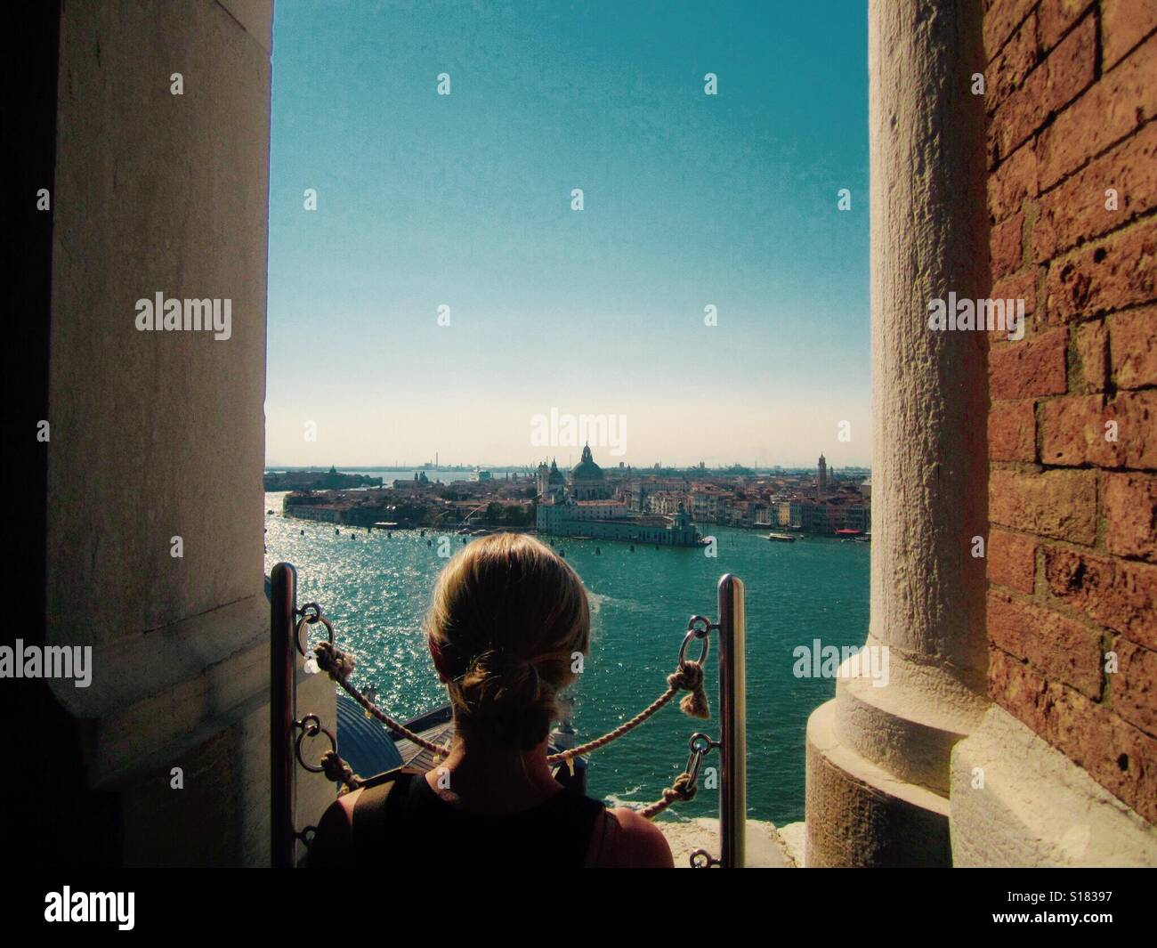 Woman looking out over Venice towards the Grand Canal Stock Photo