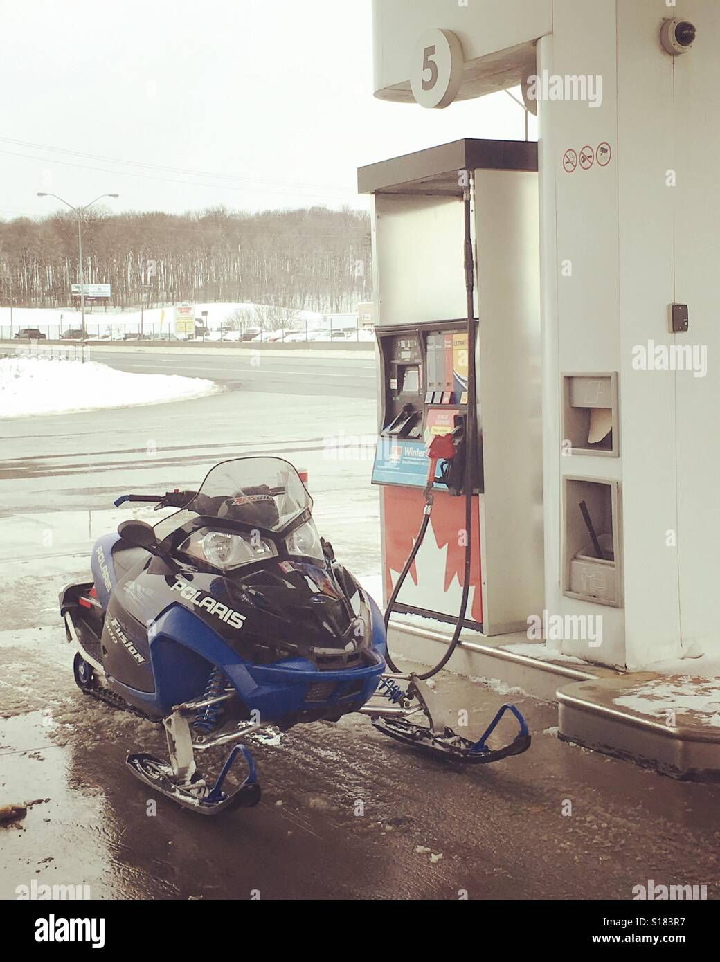 Snowmobile at at petrol station pump in Canada - Stock Image
