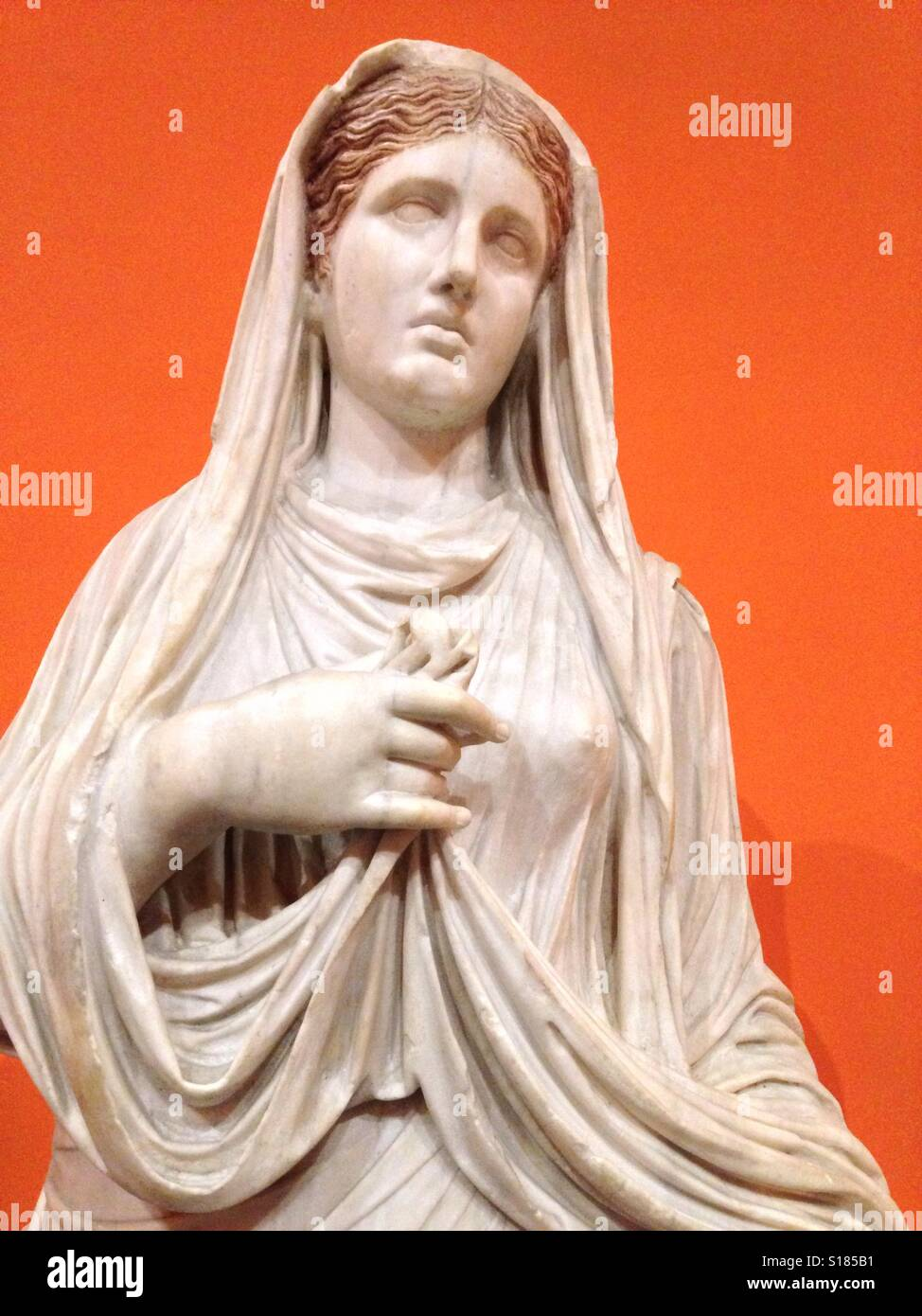 Classical marble statue of a roman girl with orange background. Stock Photo