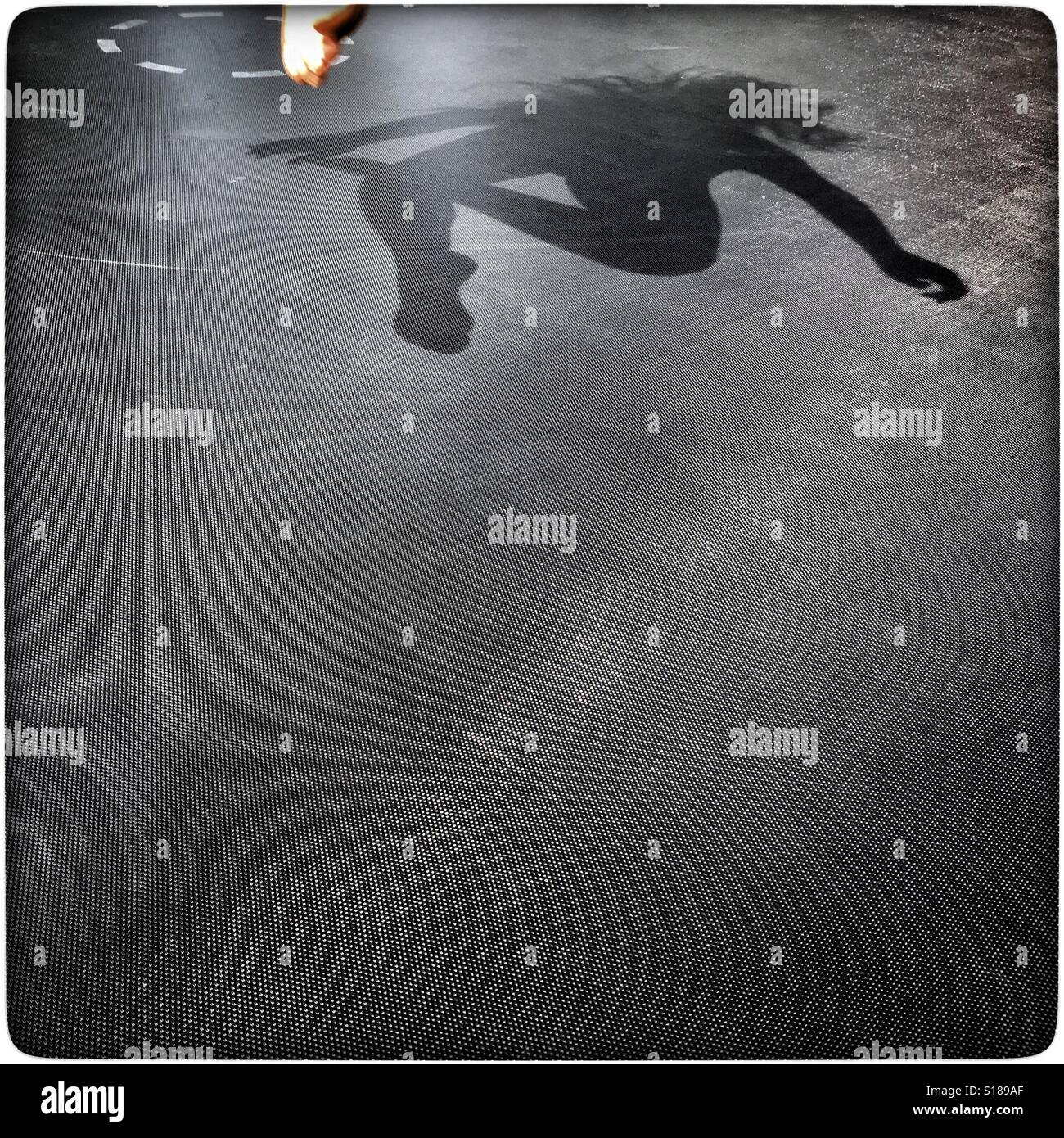 Shadow of a child bouncing on a trampoline during the Australian summer. - Stock Image