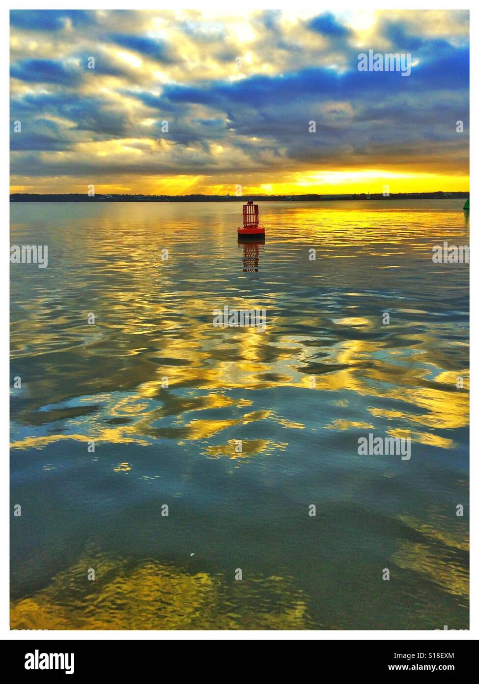Red buoy on a river, sky & clouds reflected on the water at sunset Stock Photo