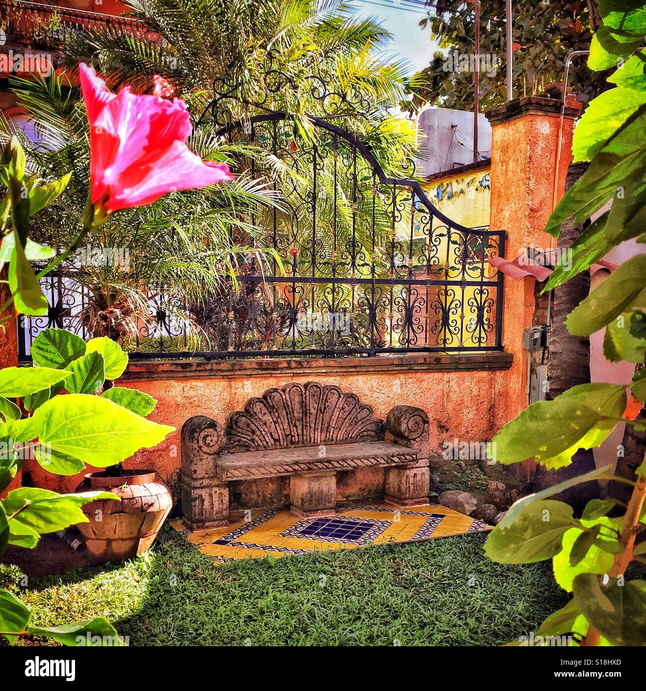 A courtyard garden featuring a bench and tropical flowers behind a a courtyard garden featuring a bench and tropical flowers behind a beautiful iron fence is a little oasis in rural nayarit mexico izmirmasajfo