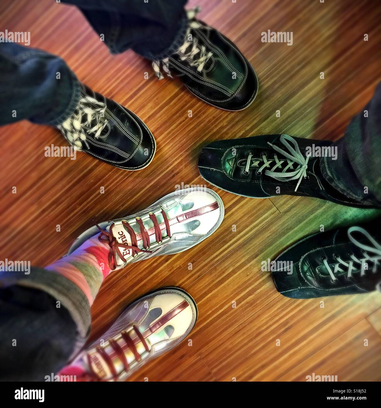 Bird's eye view of three people's feet in bowling shoes. - Stock Image