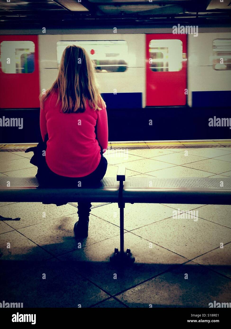 Woman sitting on a bench at London Underground Tube station watching train go by. - Stock Image