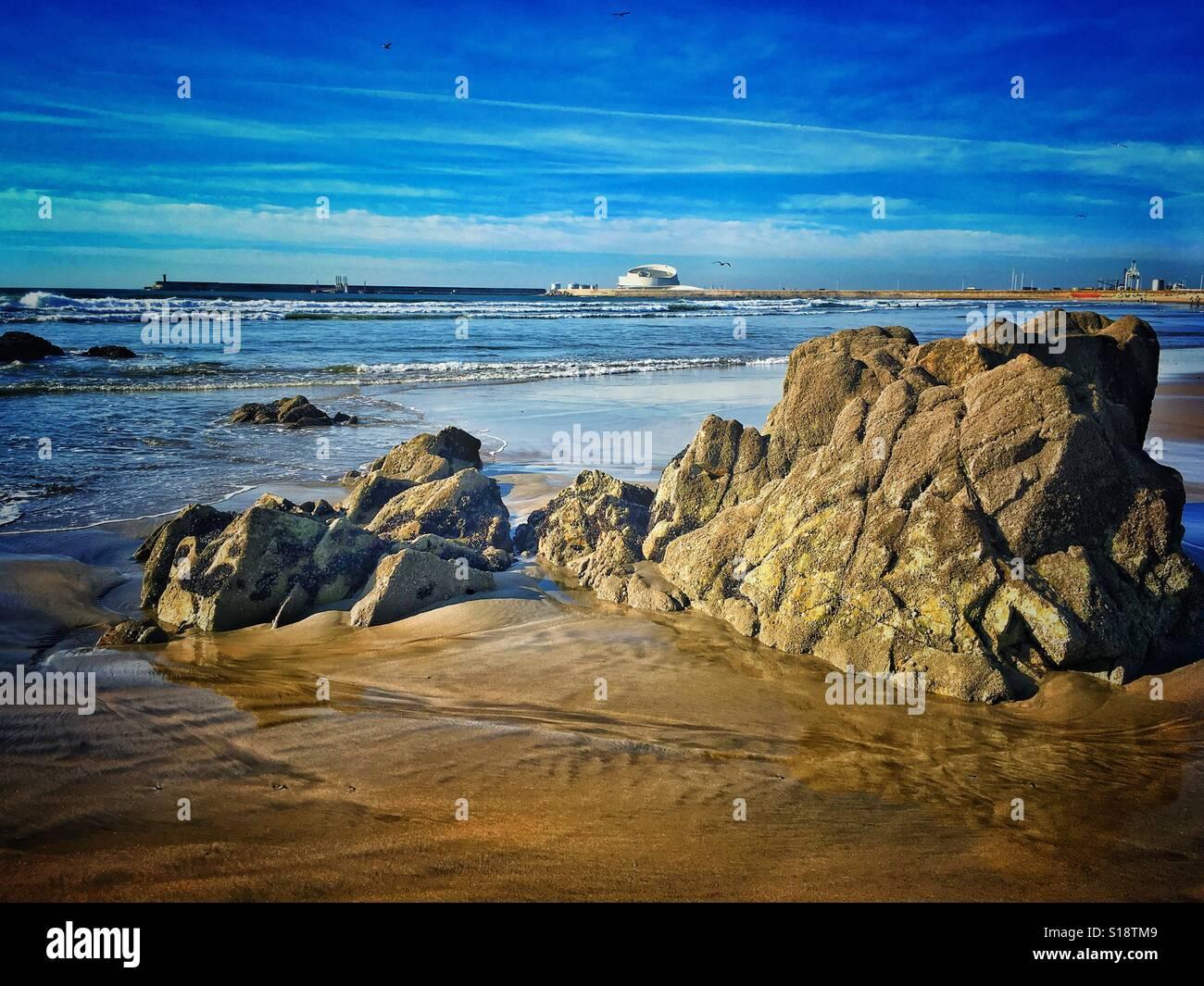 Rocks on Atlantic Ocean beach. Cruise Terminal building on background. Stock Photo