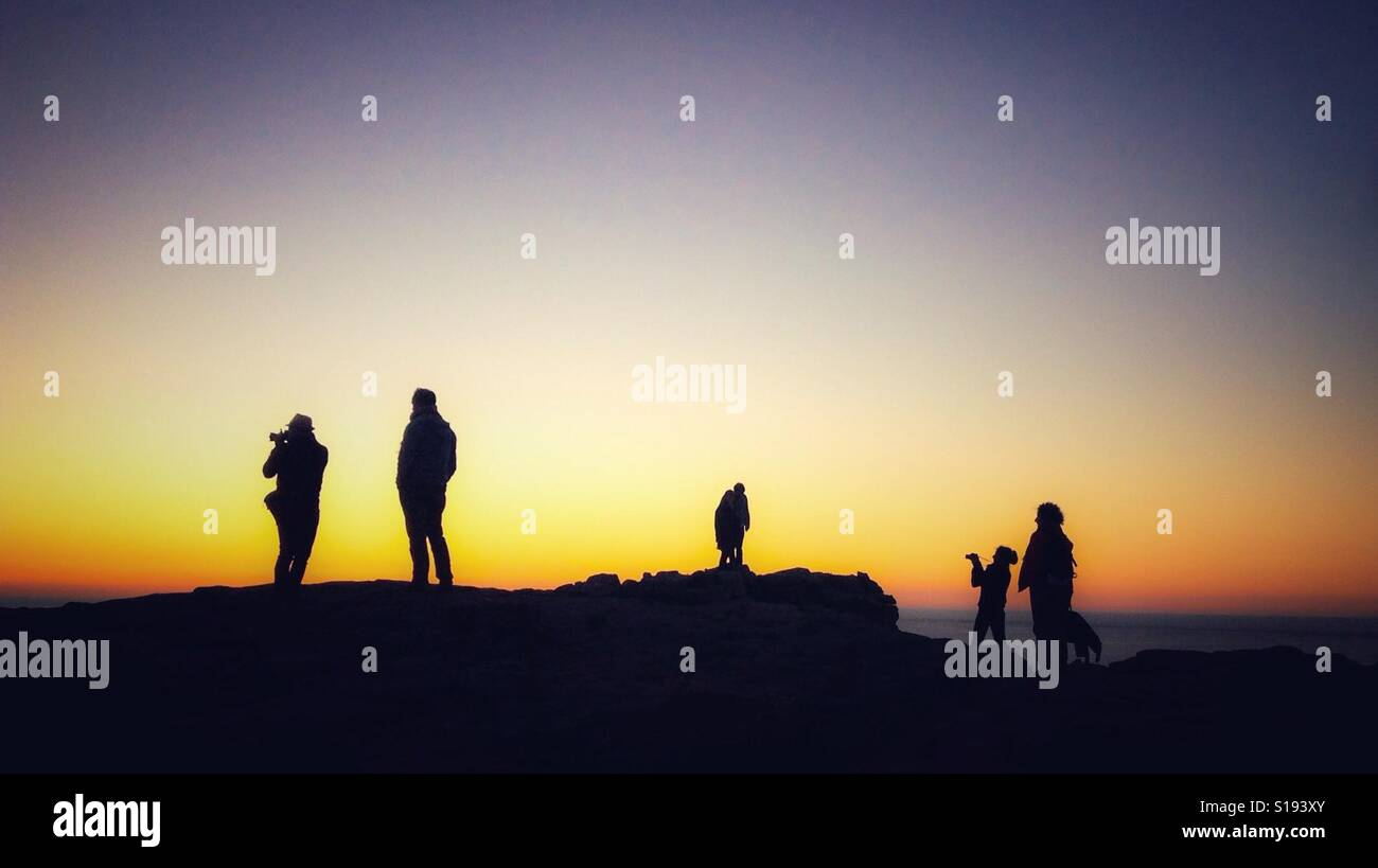Family tourists silhouetted against sunset ar the Pointe du Raz, Plogoff, France, Europe Stock Photo