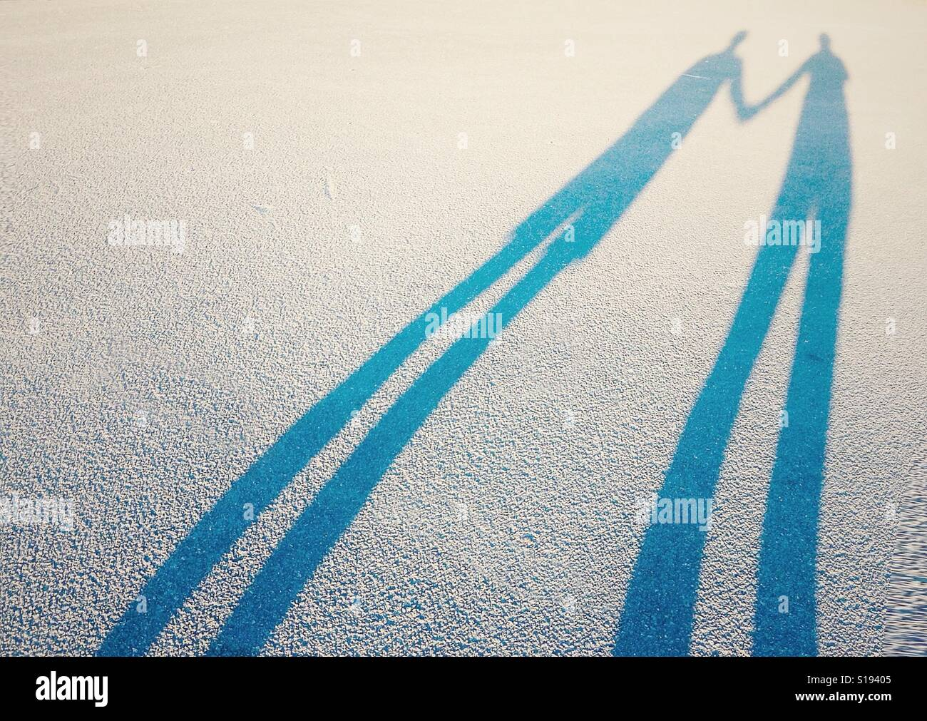 Long shadow of a couple lovers holding hands Stock Photo