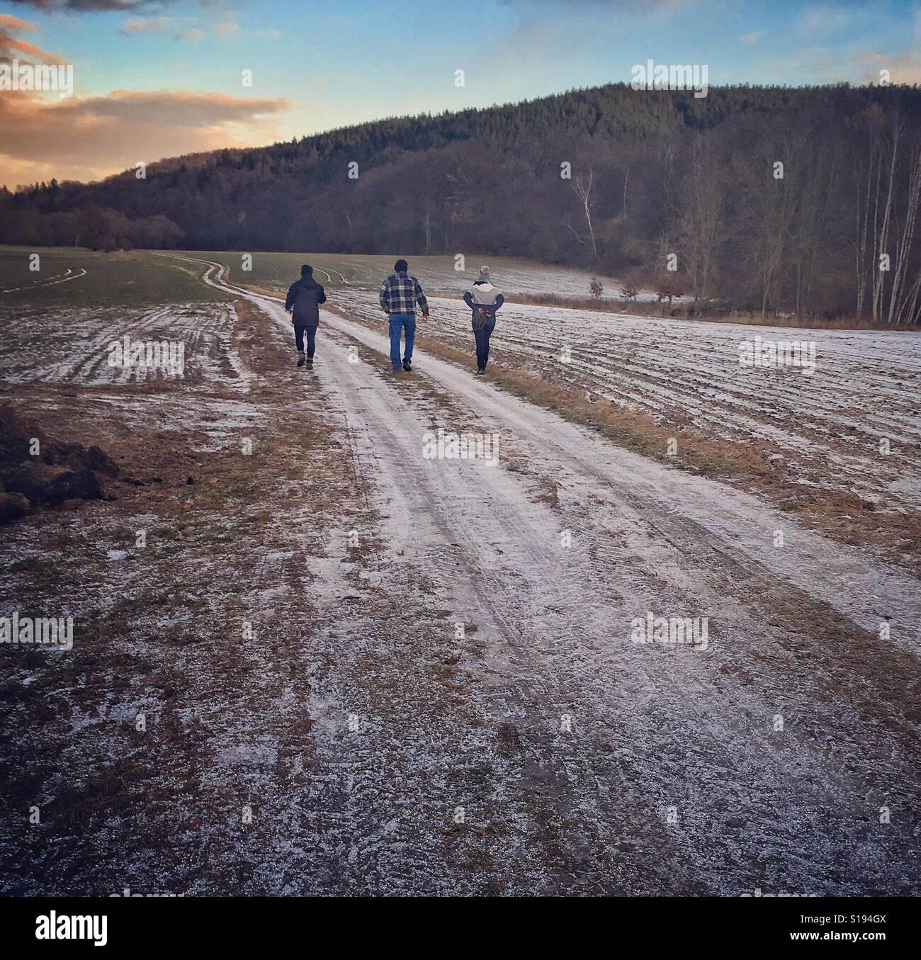 Three persons taking a family walk at winter - Stock Image