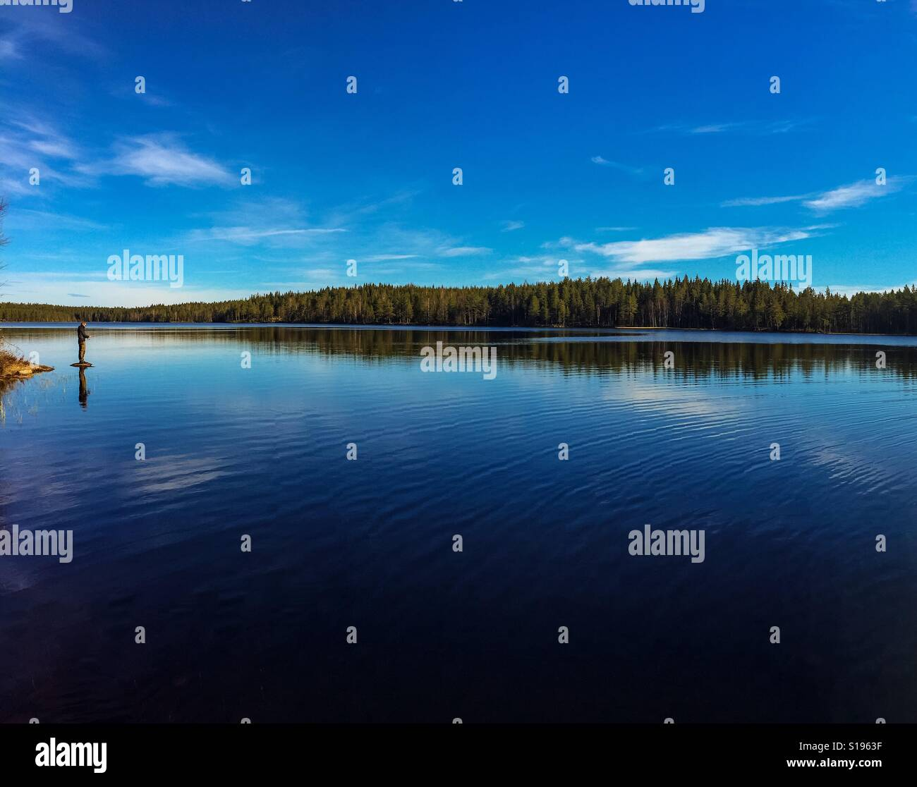 Man standing on small island and fishing in lake. Stock Photo
