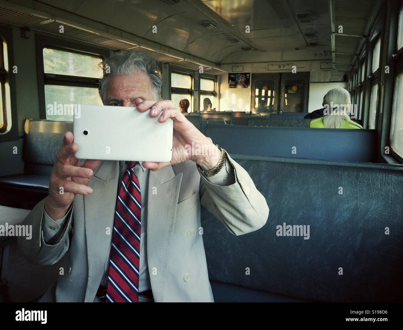 Man taking a photo with a tablet on a train in Russia - Stock Image