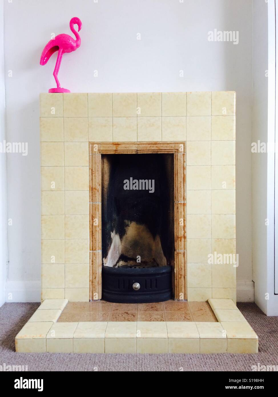 Pink flamingo on a vintage 1940s fire place. - Stock Image