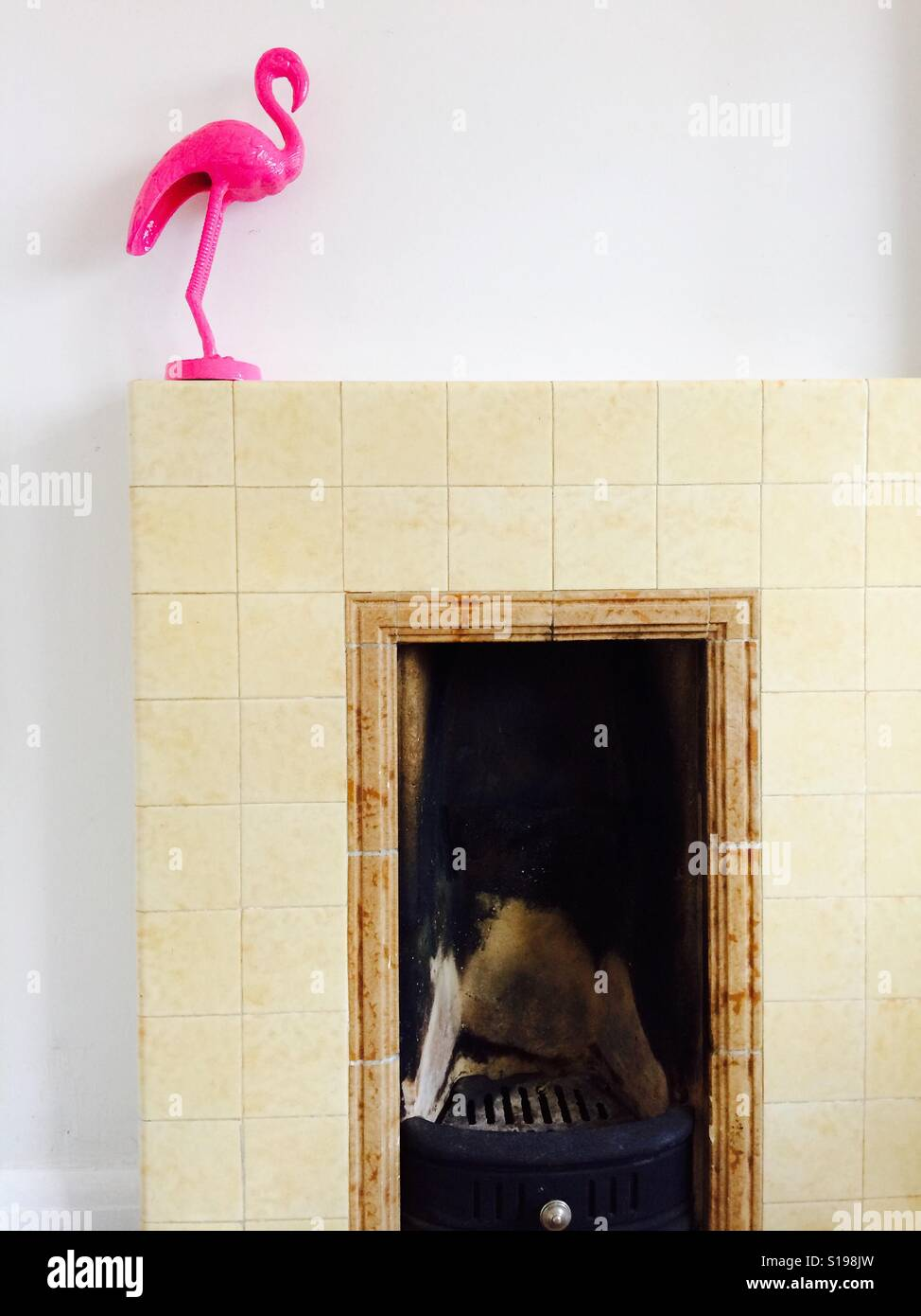 Pink flamingo ornament on a vintage 1940s tiled fireplace - Stock Image
