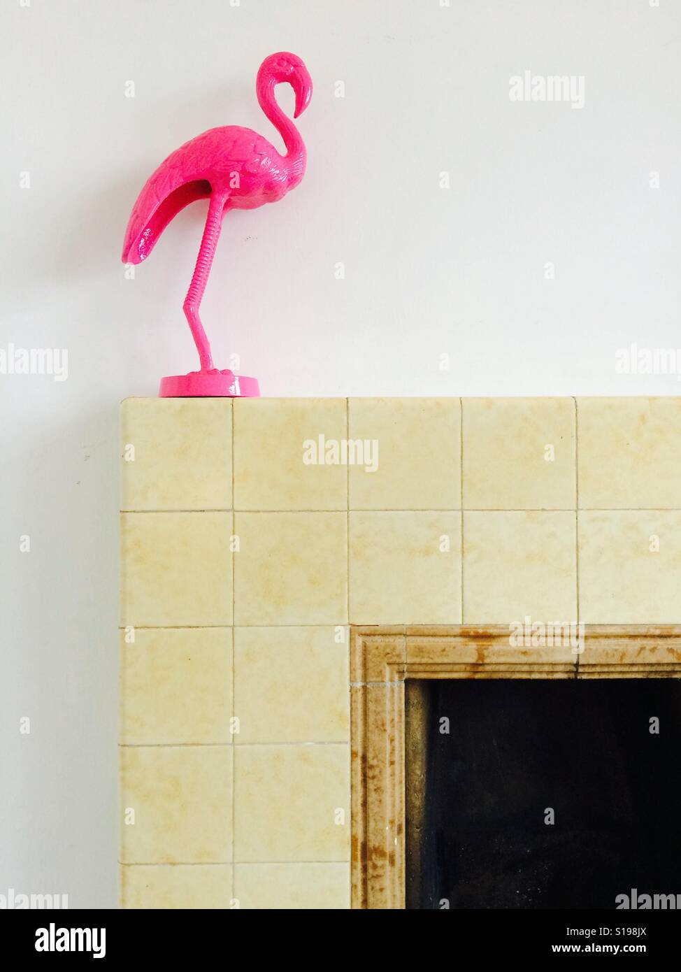 Pink flamingo on a vintage tiled 1940s fireplace - Stock Image
