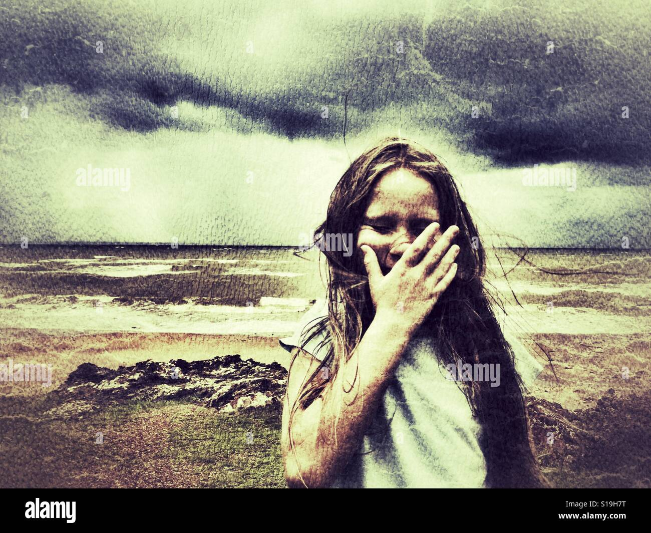 Girl crying at the beach. - Stock Image