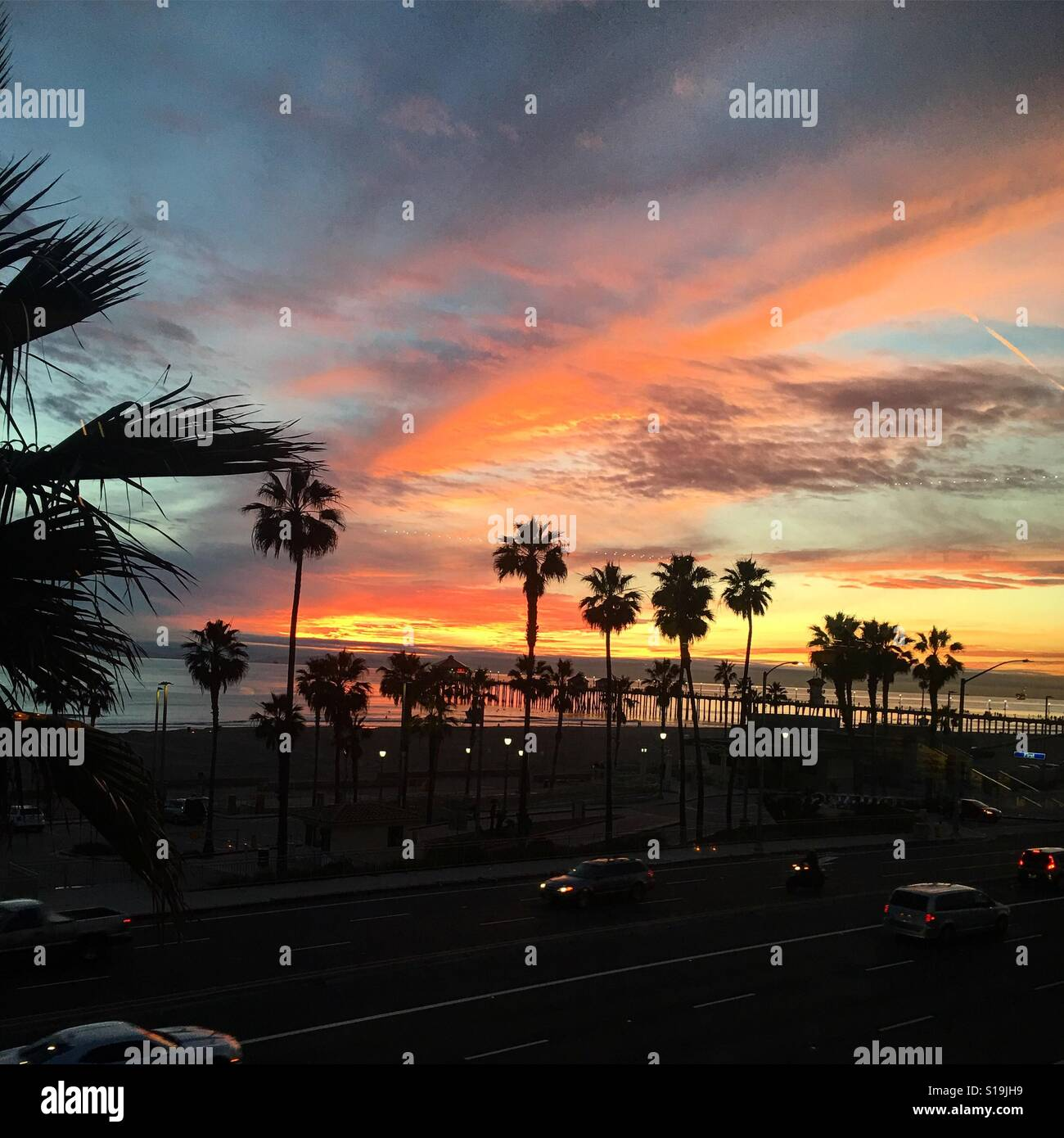 Sunset over the pier in Huntington Beach CA - Stock Image