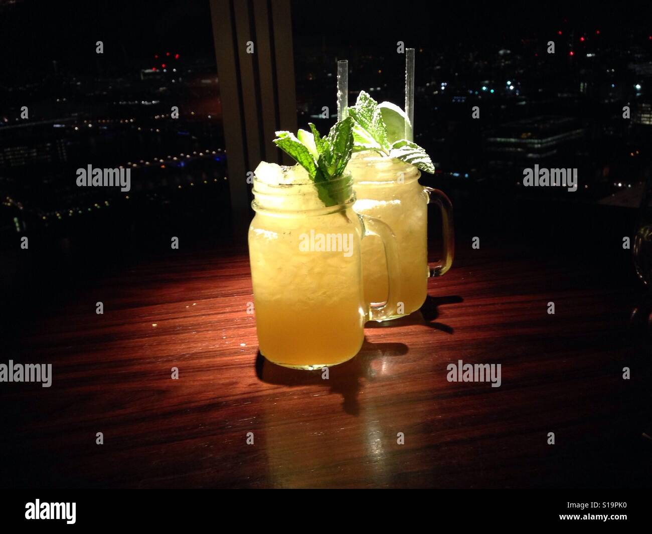 Gin cocktails under light at nighttime in London - Stock Image