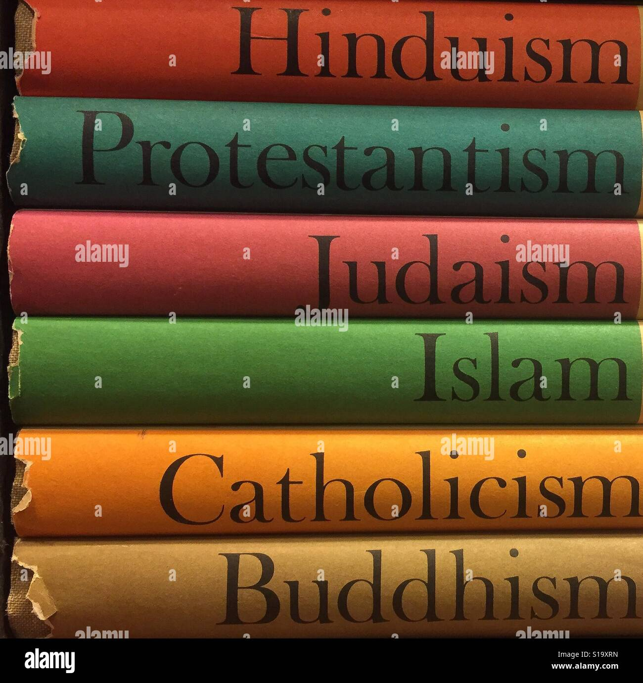 Old colorful religious books (Buddhism, Catholicism, Islam, Judaism, Protestantism, and Hinduism) stacked on top - Stock Image