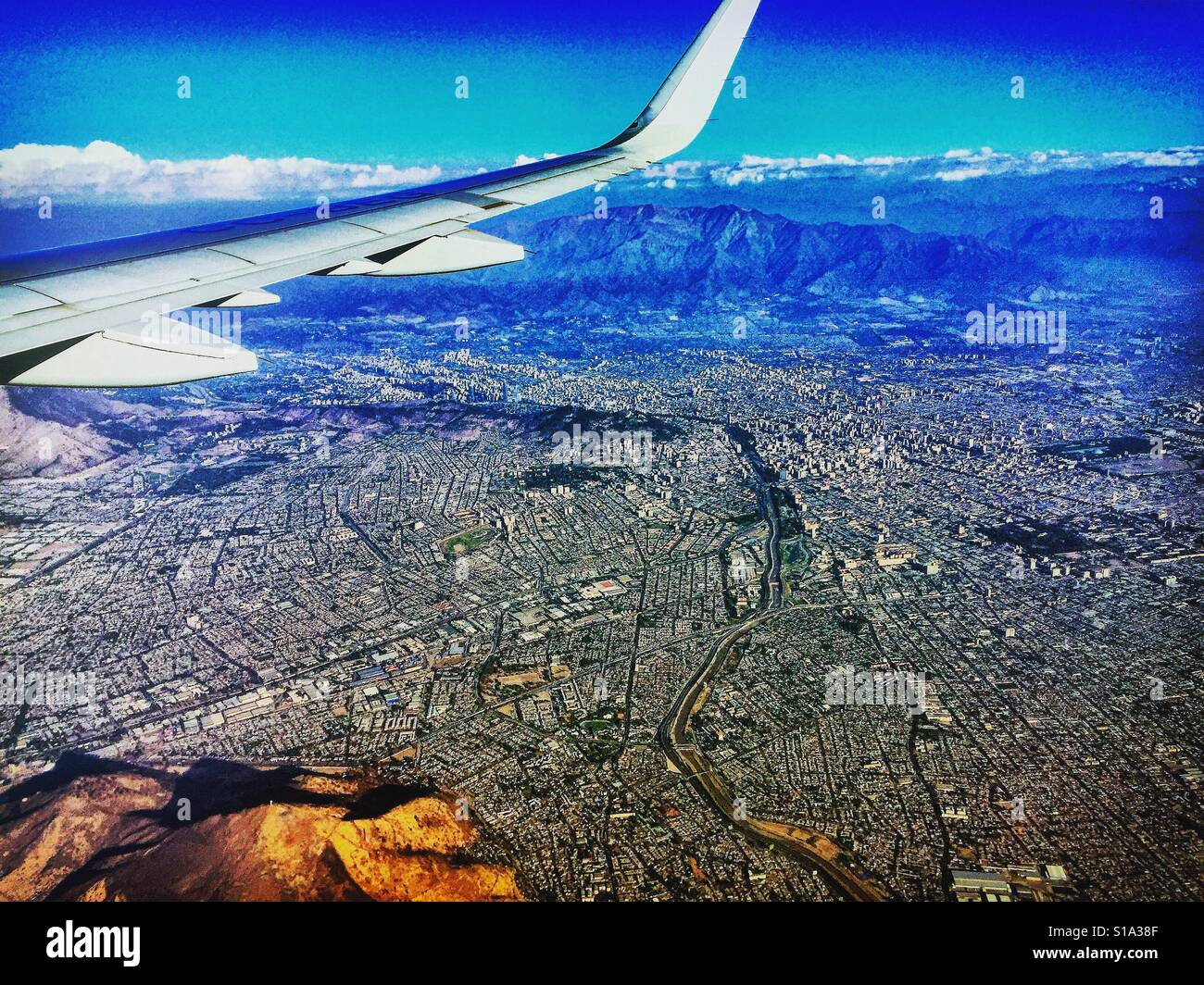 Flying over Santiago, Chile, on a clear day with the Andes in the background. Aircraft wing in the foreground. - Stock Image