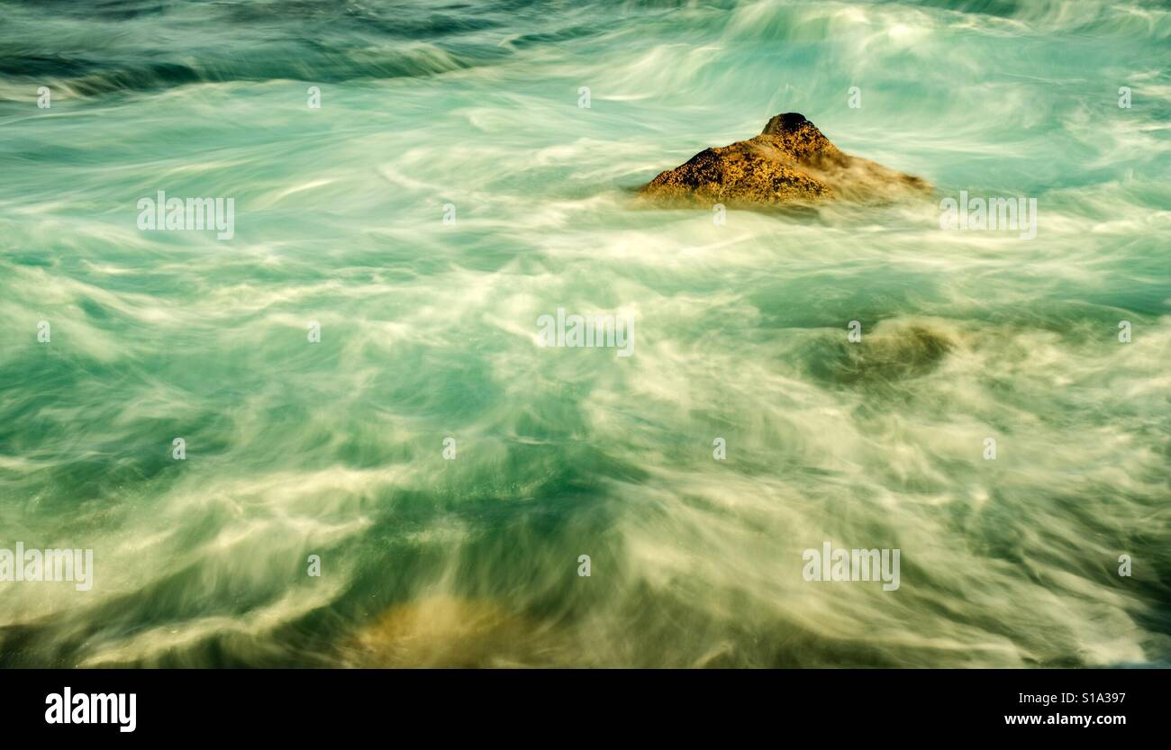surf with rock in longtime exposure - Stock Image