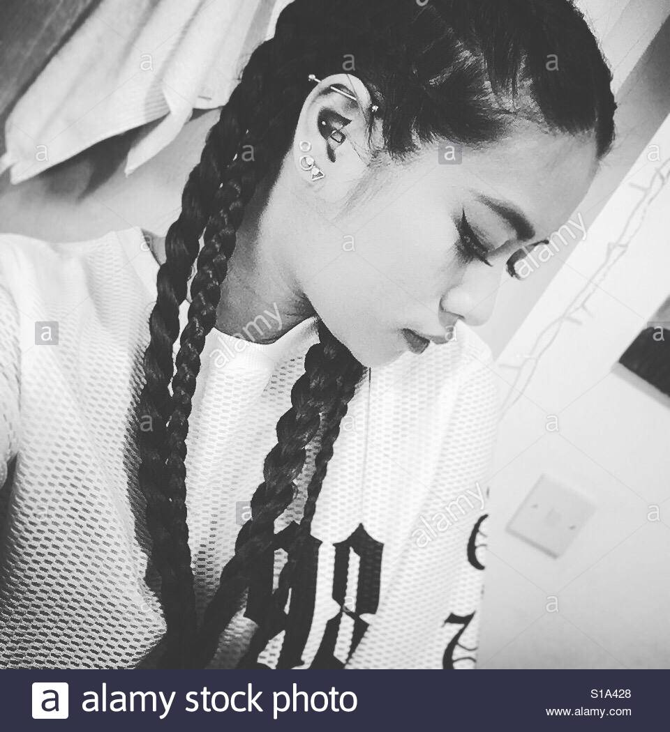 Black and white braids on an Asian with piercings - Stock Image