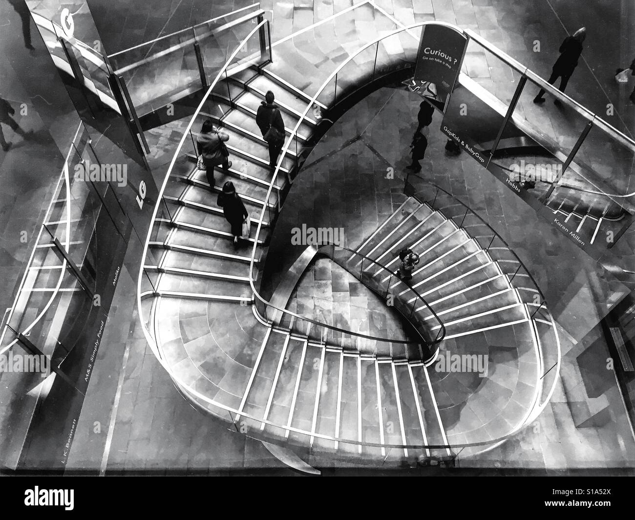 Black And White Photo Of People Walking On The Spiral Staircase At One New Change Shopping