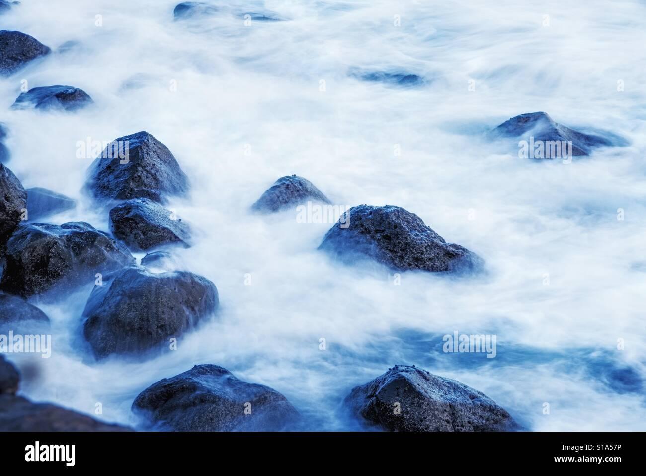atlantic ocean, volcano rocks in surf on longtime exposure - Stock Image