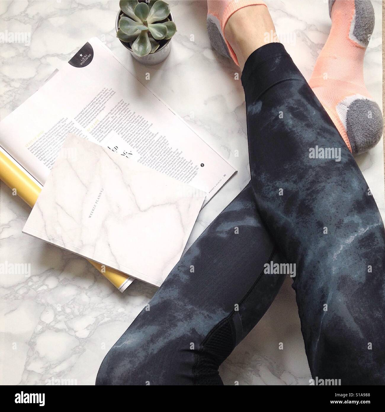 Relaxing and reading in leggings on a marble floor - Stock Image