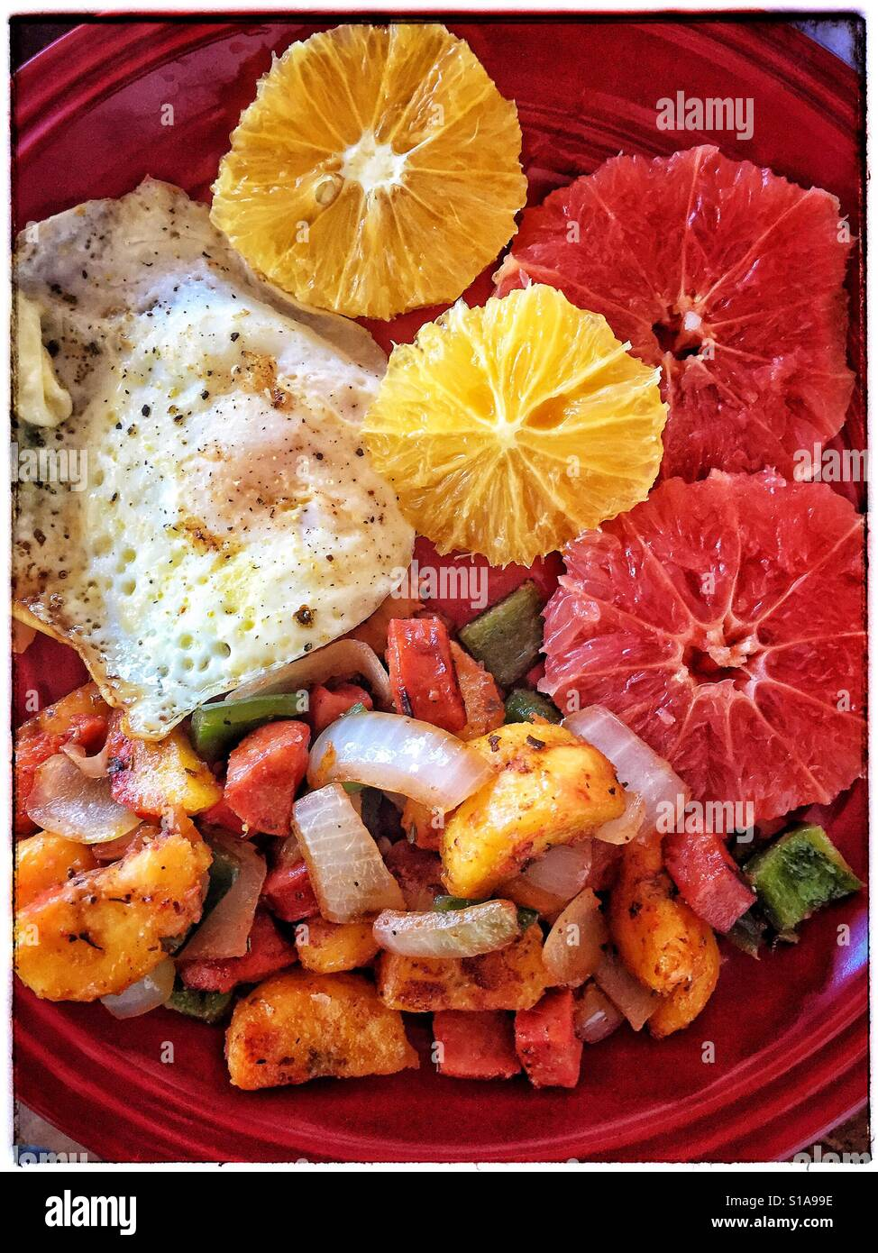 A plate is filled with a colorful variety of delicious breakfast foods including a fried egg, citrus slices, and Stock Photo
