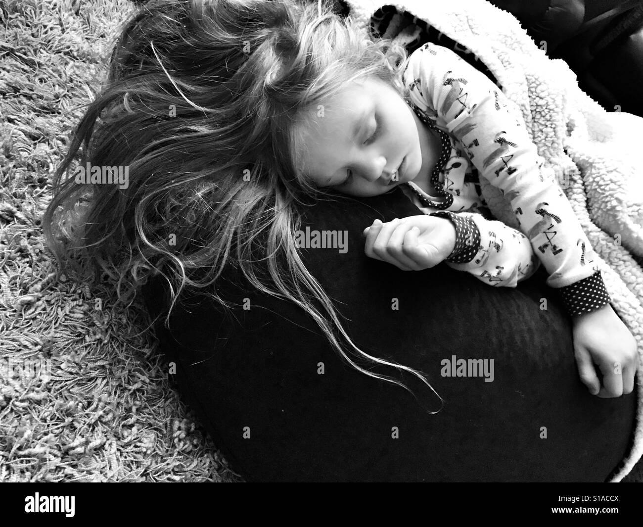 Little girl sleeping on a bean bag Stock Photo