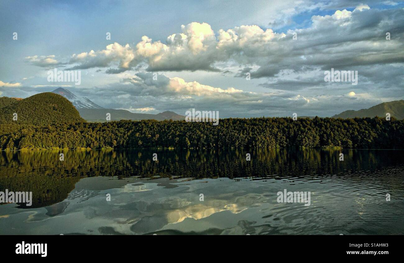 The sun is about to set on a beautiful Andean lake in southern Chile. An interesting cloudscape reflects in the - Stock Image