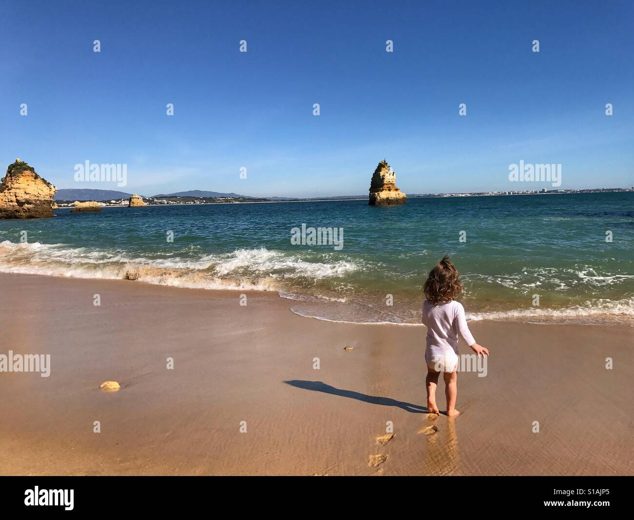 Toddler playing on the beach Algarve Portugal - Stock Image