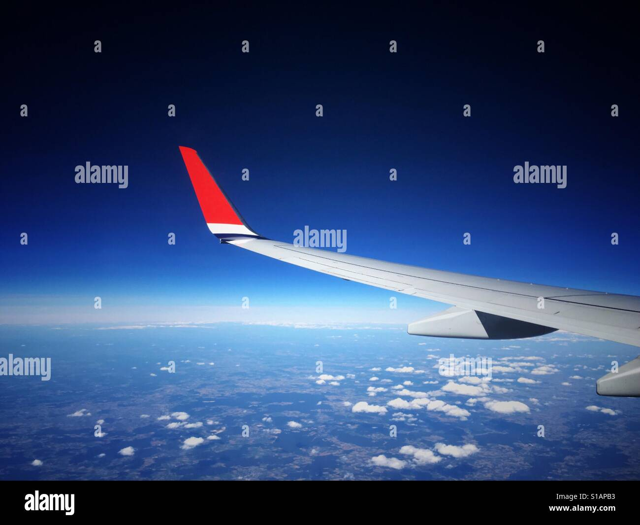View through an aeroplane window of an airliner wing with a bright red wing tip, flying high above the clouds against - Stock Image