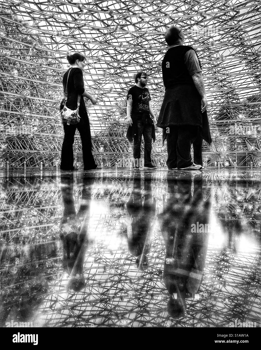 Three people looking up and reflected on the floor of The Hive, an art installation telling the story of honey bees - Stock Image