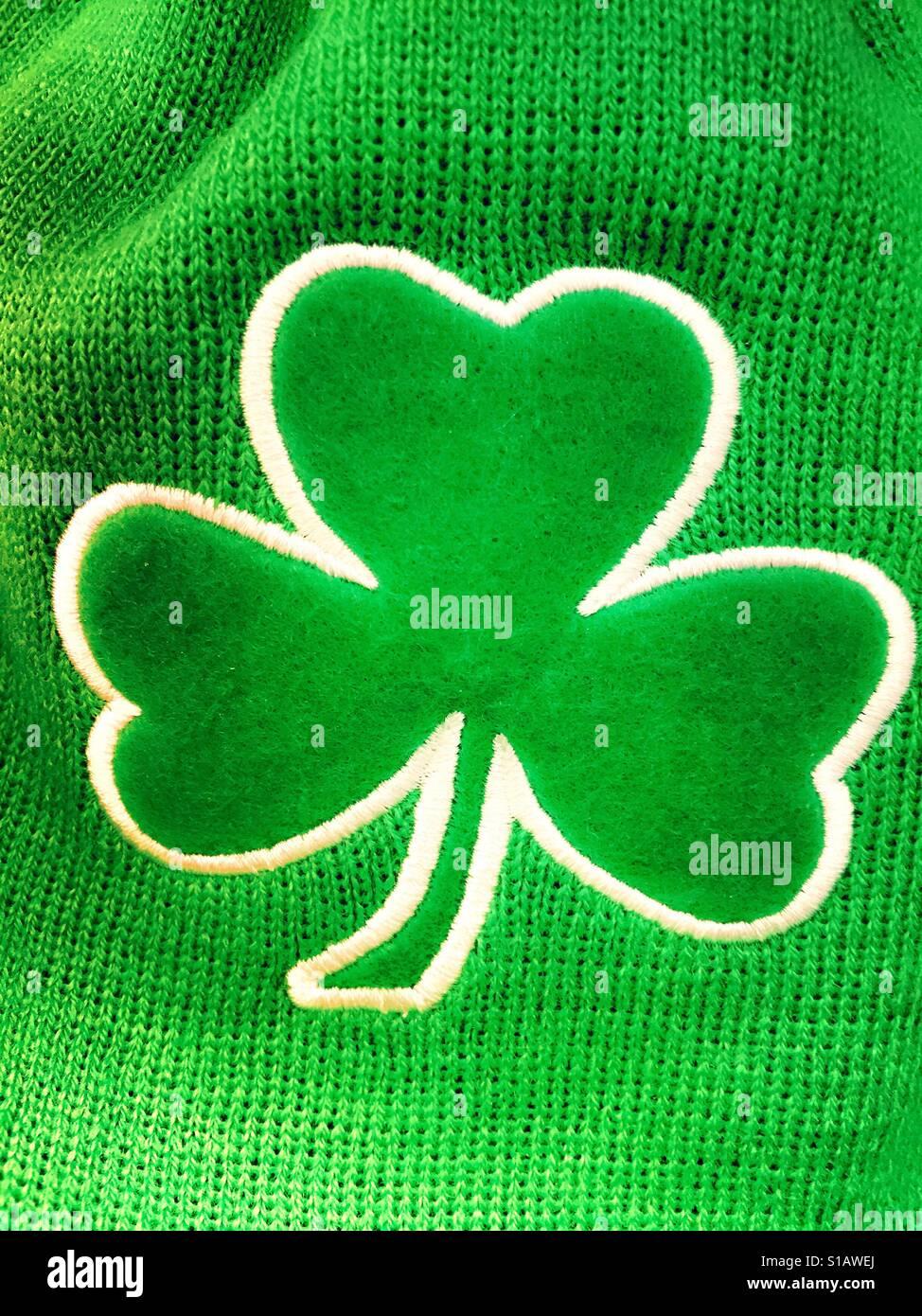 Shamrock sewn onto green St. Patrick's Day merchandise, USA - Stock Image