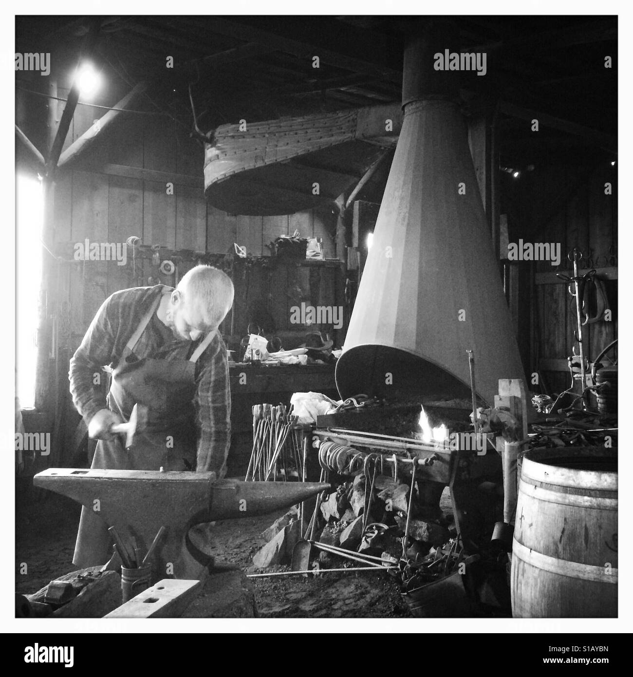 A blacksmith works in his workshop on Main Street. Columbia State Historic Park, Columbia, Tuolumne County,  California, - Stock Image